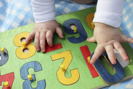 young child playing with a number puzzle