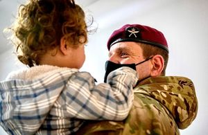 Commanding Officer First Battalion The Royal Gurkha Rifles holds an Afghan evacuee