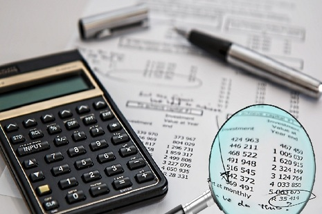 Image of calculator, pen, magnifying glass and sheet with figures