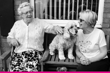 Picture of two women having a conversation on a bench with a dog between them