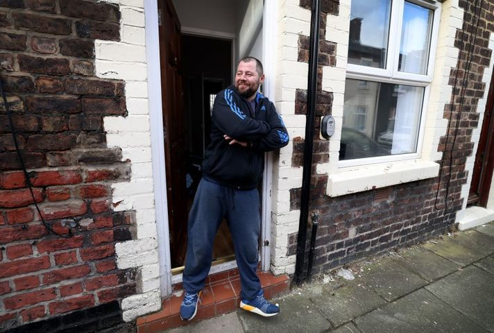 Peter, a white man, stands on the doorstep of his new home, looking down the street. He is smiling.