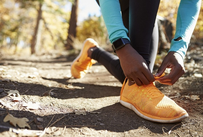 Close up of runner tying shoes, wearing fitness tracker