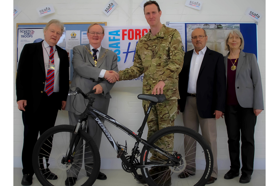 Lieutenant Colonel Oli Stokes receives a bike from the Mayor of the Royal Borough of Greenwich