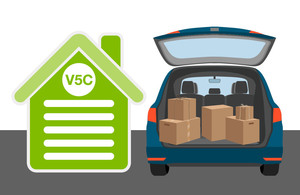 Car with a boot open with moving boxes inside and a V5C document