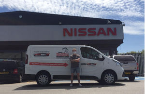 Images shows a man standing in front a Nissan van which is in front of a Nissan logo. The van has the logo for the Walking with the Wounded charity on it. The man has his arms crossed and is looking directly at the camera.