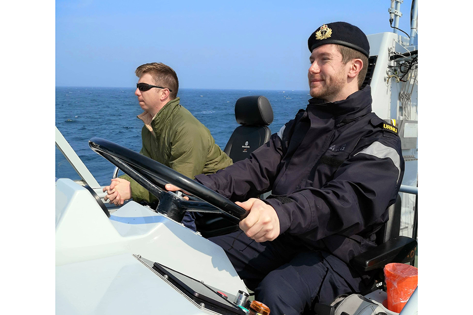Simon Chapman sits smiling at the wheel of a small ship in his Navy uniform. A person in a green coat and sunglasses sits beside him