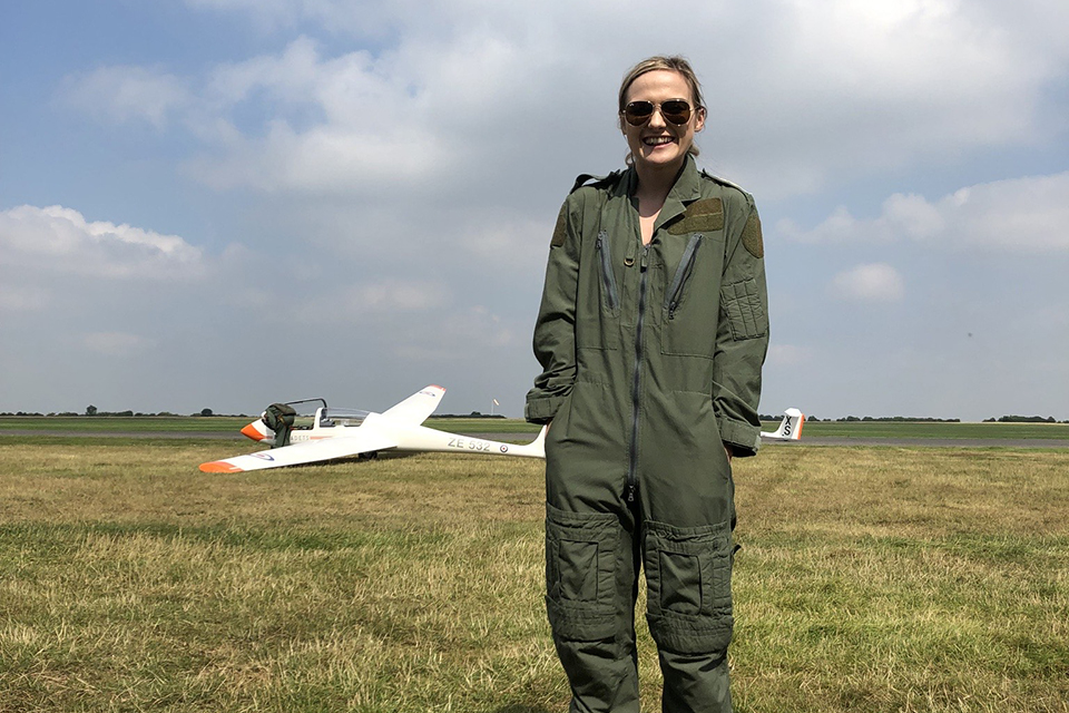 Polly stands smiling in an airfield wearing flight gear with her hands in her pockets and a glider behind her.