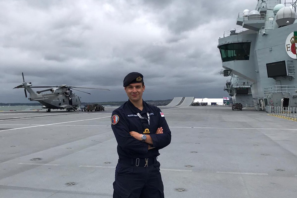 SLT Ewing proudly stands on the grey deck of a ship, with a helicopter, the forward bridge and the ski-jump ramp in the background