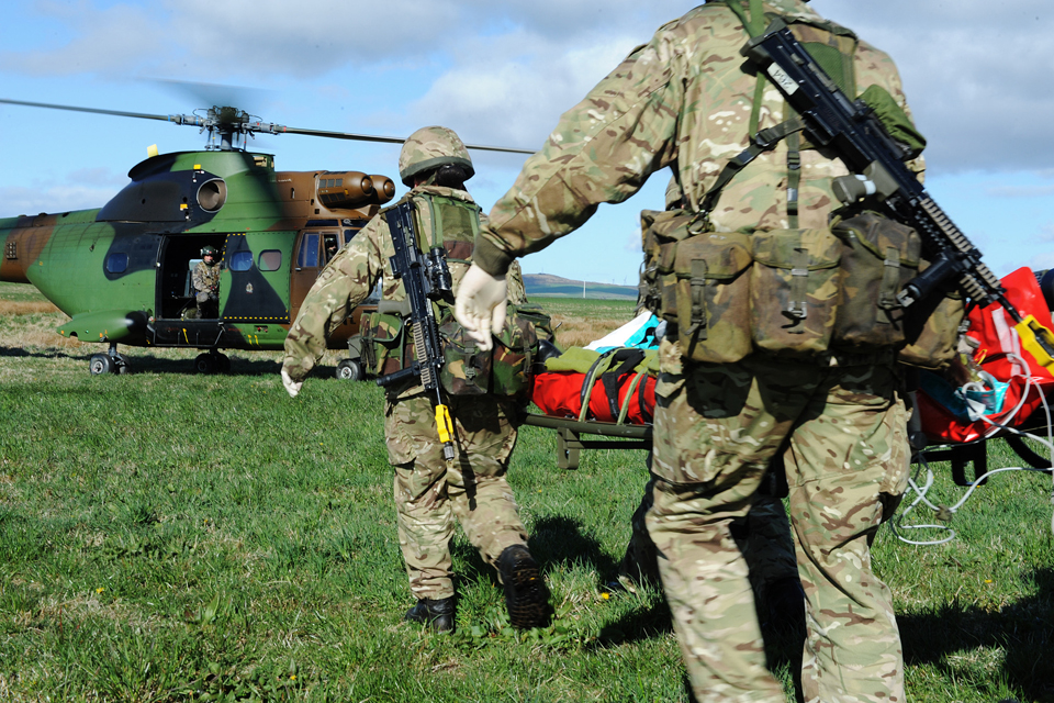 The simulated casualty is carried by stretcher to a waiting French Puma helicopter