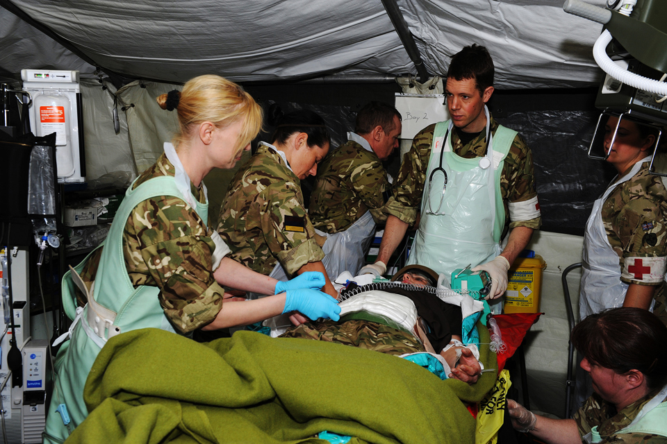 Medics treat the simulated casualty inside the field hospital