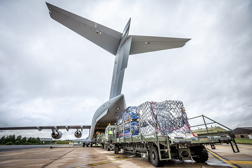 Image depicts a cargo pack in front of the back of an open C-17 aircraft.