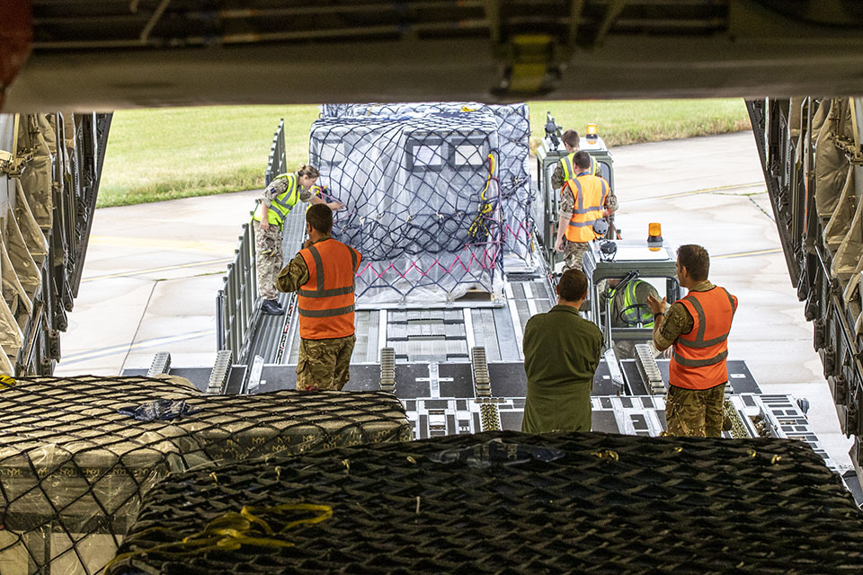 Image depicts cargo being loaded onto an aircraft by two men.
