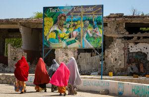 Somali woman walk past a billboard mural. AU-UN IST PHOTO / STUART PRICE