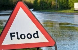 flood sign in front of a flooded road