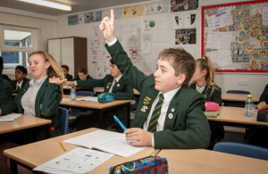 Secondary school student raising his hand in class