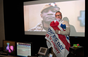 Ray Winstone wrapped in an Armed Forces Day flag [Picture: Sergeant Jez Doak, Crown copyright]