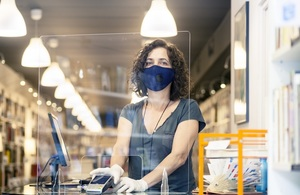 Woman behind a shop counter wearing a face covering