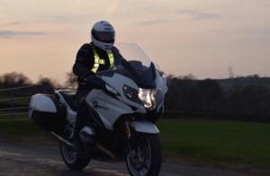 Image shows a motorcyclist riding on a country road