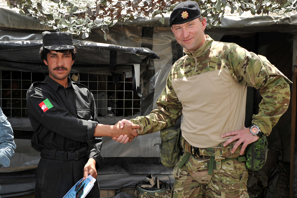 Major Kenneth Nielsen shakes hands with a member of the Afghan Uniform Police