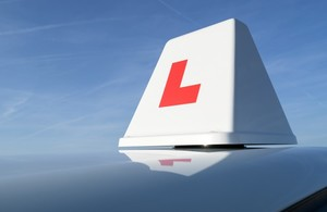 Photo of an L plate on top of a driving school car