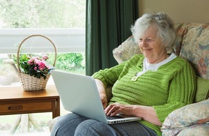 An older woman sitting in an armchair using a laptop