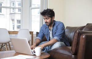 Photo of a man, sat on a sofa, using a laptop