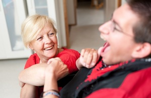 A carer talking to a man in a wheelchair