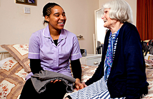 A carer with an older person in a residential care home