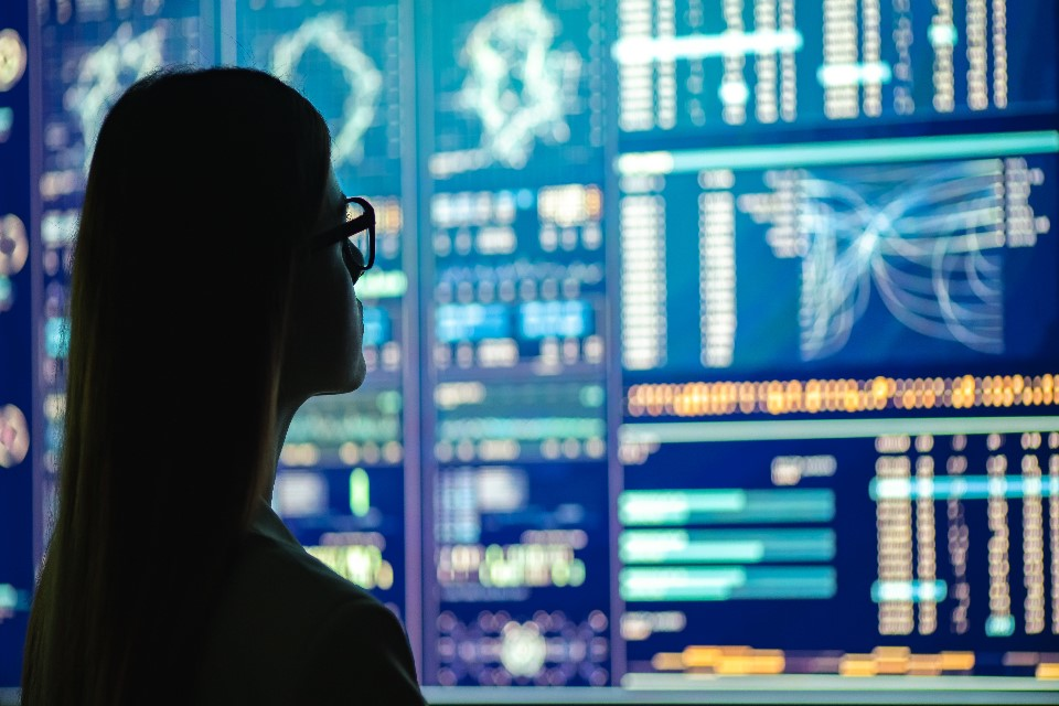 Photo of a woman looking at data on screens