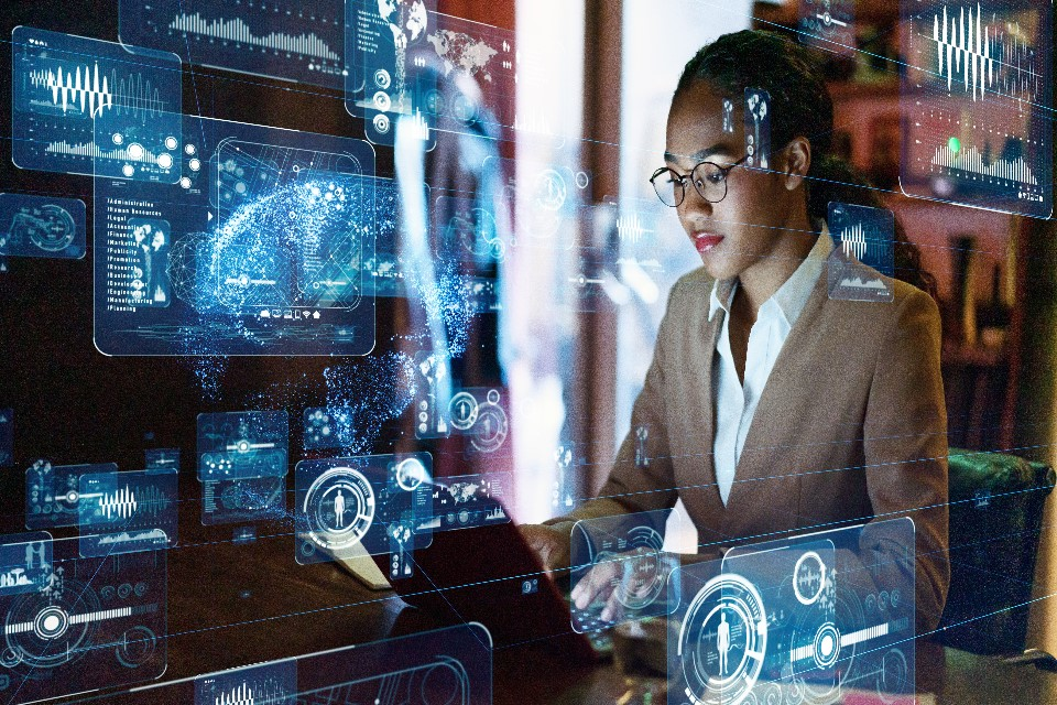 Photo of a woman at a computer with data graphics