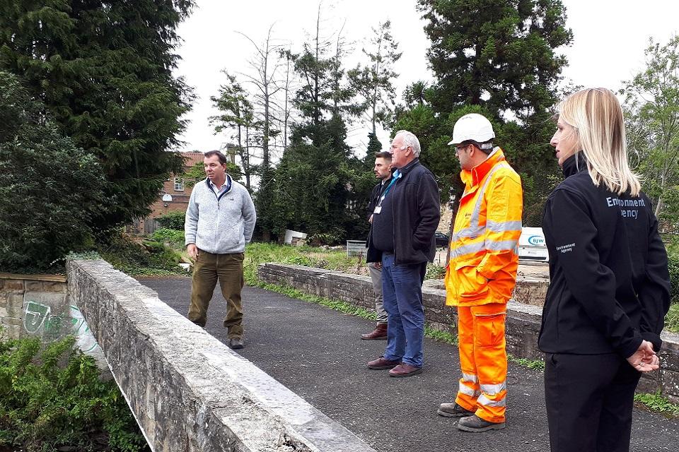 Image shows Hexham MP Guy Opperman being shown around Ponteland flood scheme