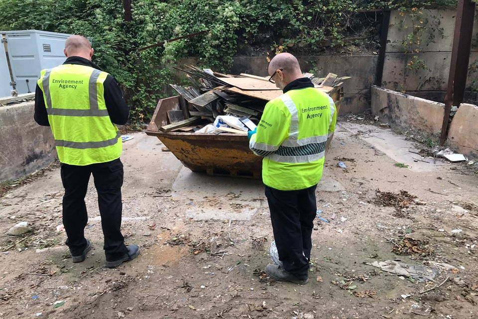 Officers looking at a skip full of waste and taking notes.