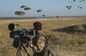 A British Army soldier stands by a weapon in the foreground as paratroopers drop into the field behind him in the background