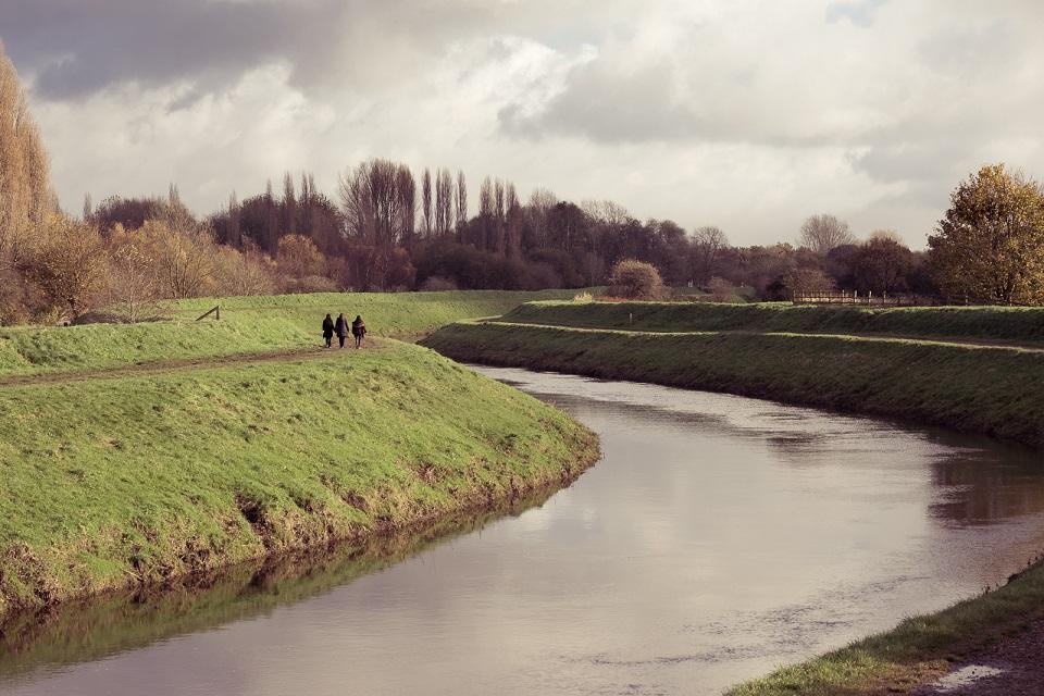 People walking alongside River Mersey