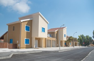 Row of newly built homes on a sunny residential street.