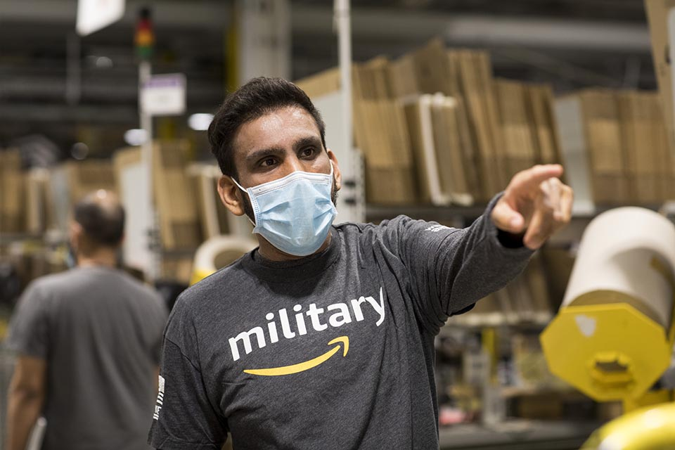 Man wearing a t-shirt with the amazon logo and the word 'military' written across the front.