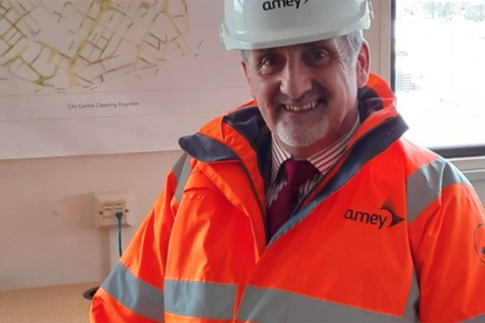 Mark smiling straight at the camera wearing a florescent orange coat and white hard hat.