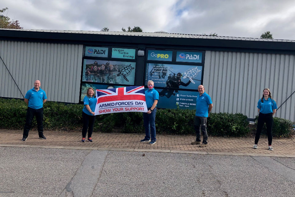 Members of staff from the Diving School standing outside and holding the Armed Forces Covenant flag.