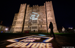 A projection of the Here for Culture logo on the side of Dover Castle