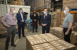 The Defence Secretary stands with staff from The Poppy Factory in their Richmond warehouse