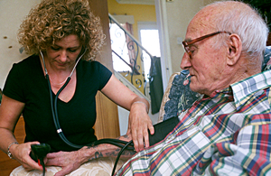 Carer taking an older man's pulse in his home