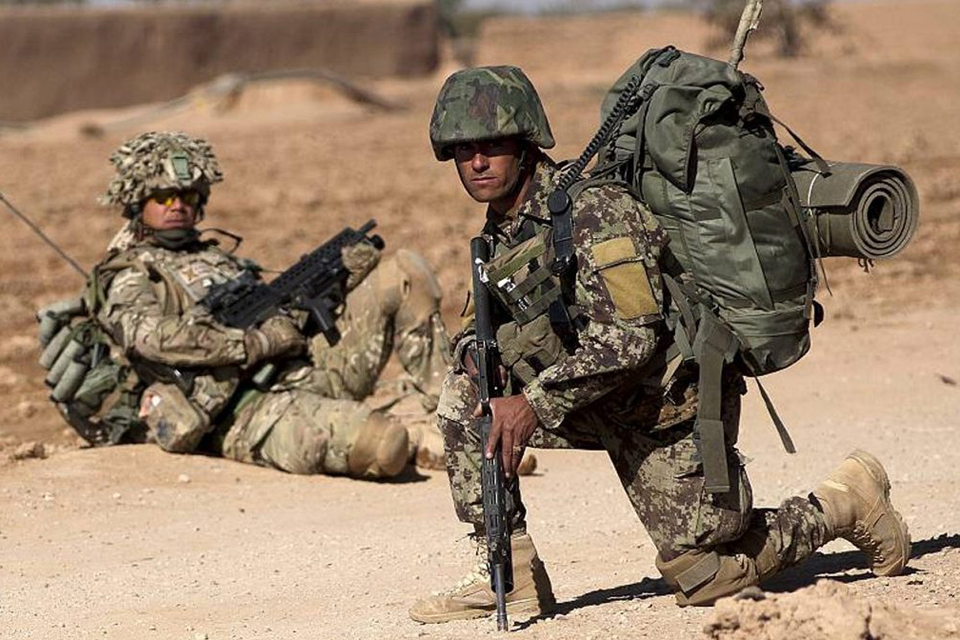 British and Afghan soldiers pause during a patrol