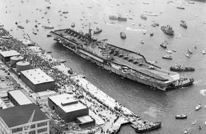 Aerial view of the aircraft carrier HMS Hermes, about to berth alongside at Portsmouth Harbour on her return from the Falklands on 21 July 1982 [Picture: Crown copyright - IWM (FKD 684)]
