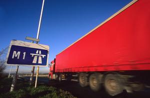 Lorry passing road sign stating start of M1 motorway near Leeds, Yorkshire, UK
