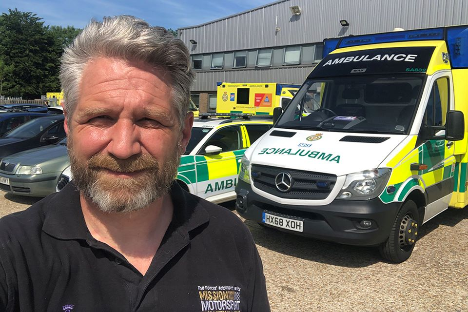 James Cameron standing in front of NHS ambulances smiling at the camera.