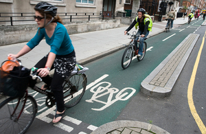 Cyclists cycling down a cycle lane on a busy street.