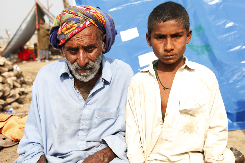 Waseem and his grandfather in front of a temporary shelter made from heavy-duty plastic sheeting. Picture: Russell Watkins/DFID