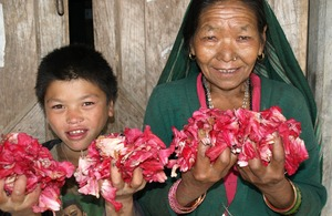 A woman and boy holidng Rhododendron flowers. Picture: Sibongile Pradhan/LFP/DFID