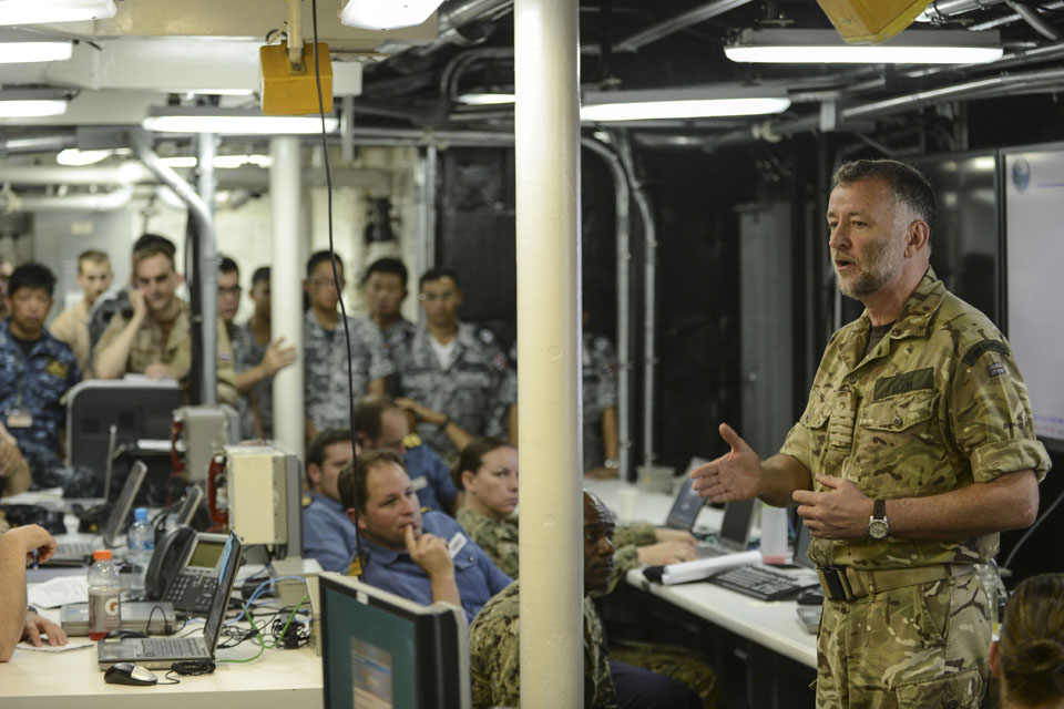 Captain Andy Elvin speaks to multinational Service personnel