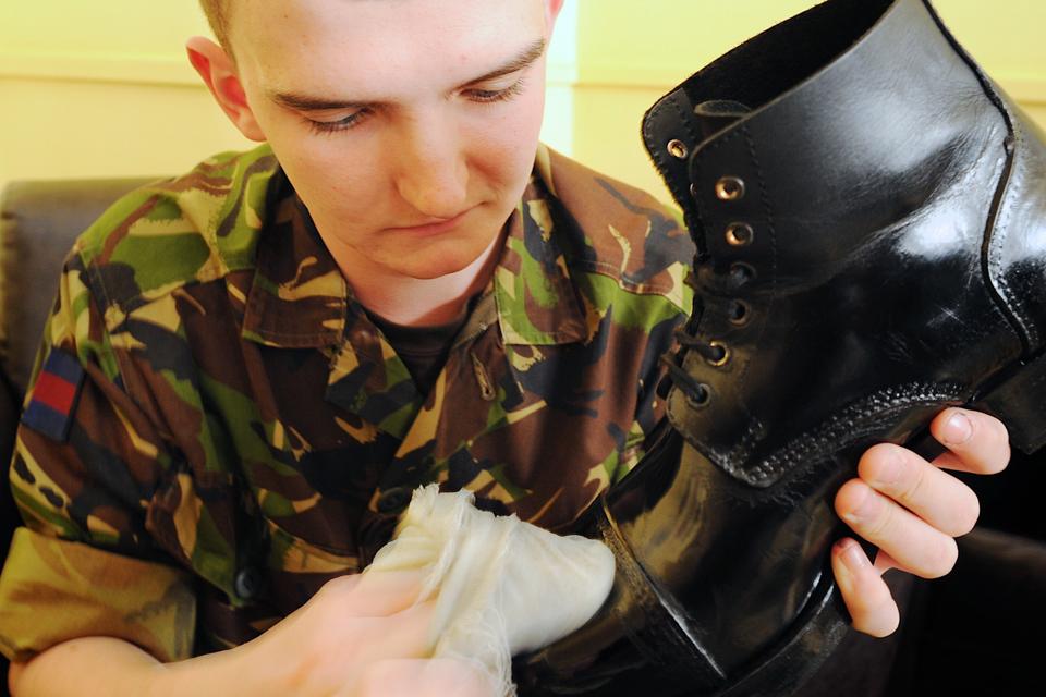 A guardsman polishes his boots